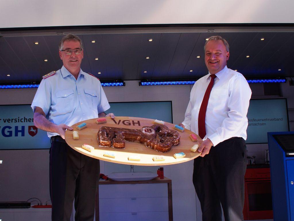 LFV-Präsident Karl-Heinz Banse und der VGH-Vorstandsvorsitzende Hermann Kasten mit dem symbolischen Schlüssel des neuen VGH-Brandschutzmobils. (Foto: LFV-NDS Rebmann)